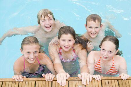 ni�os nadando: Cinco j�venes amigos en la piscina sonriendo Foto de archivo
