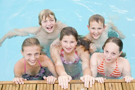 kids swimming pool: Five young friends in swimming pool smiling Stock Photo