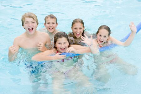 Five young friends in swimming pool playing and smiling photo