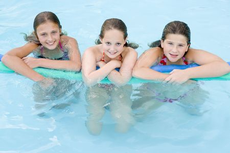 Three young girl friends in swimming pool with pool noodle smiling Stock Photo - 3486699