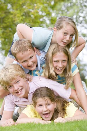 Five young friends piled on each other outdoors smiling photo