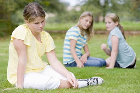 Two young girls bullying other young girl outdoors photo