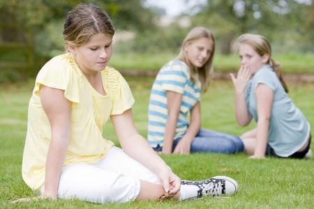 peer to peer: Dos muchachas j�venes intimidaci�n otra ni�a al aire libre
