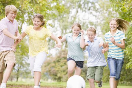 chicas divirtiendose: Cinco j�venes amigos jugando al f�tbol Foto de archivo