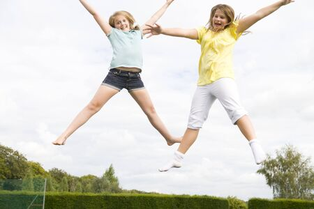 Two young girls jumping on trampoline smiling Stock Photo - 3485843