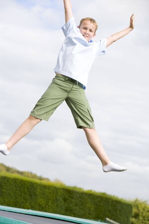 Young boy jumping on trampoline smiling photo
