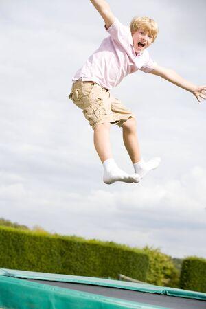 ni�o saltando: Joven saltando en trampol�n sonriente