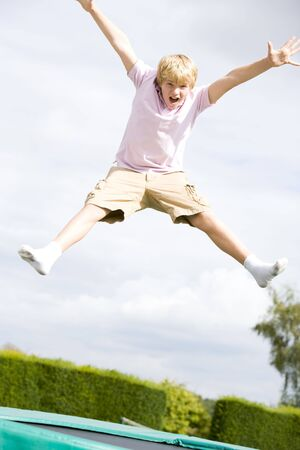 Young boy jumping on trampoline smiling Stock Photo - 3485791