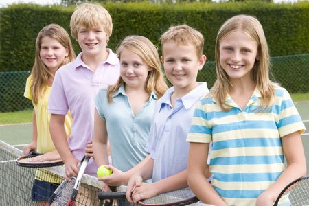 children playing outside: Five young friends with rackets on tennis court smiling