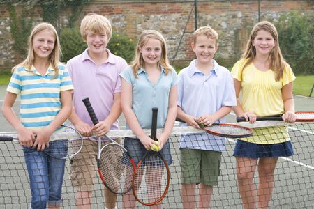 Five young friends with rackets on tennis court smiling photo