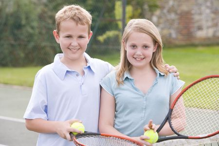 Two young friends with rackets on tennis court smiling Stock Photo - 3486972