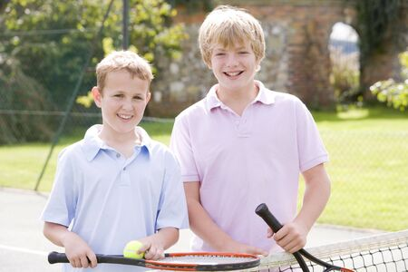 Two young male friends with rackets on tennis court smiling photo