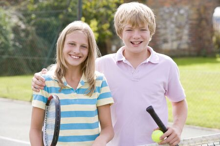 Young couple with rackets on tennis court smiling photo