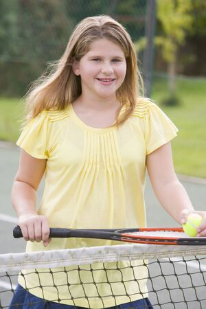 Young girl with racket on tennis court smiling photo
