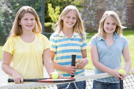 Three young girl friends with rackets on tennis court smiling photo