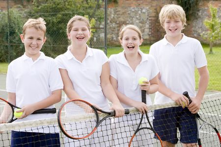 children playing outside: Four young friends with rackets on tennis court smiling Stock Photo