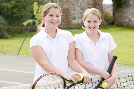 Two young girl friends with rackets on tennis court smiling photo