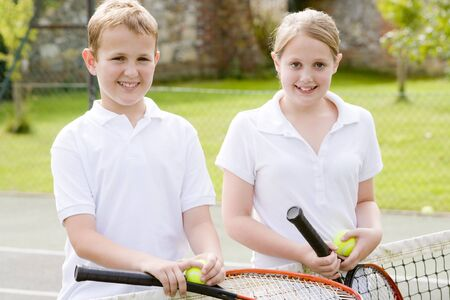 Two young friends with rackets on tennis court smiling photo