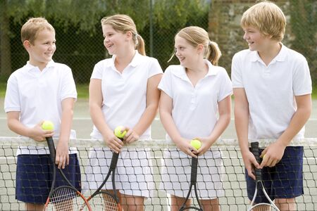 male tennis players: Four young friends with rackets on tennis court smiling Stock Photo