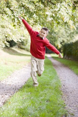Young boy running on a path outdoors smiling photo
