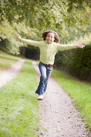 tween boy: Young girl running on a path outdoors smiling