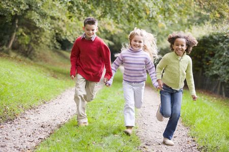 children playing outside: Three young friends running on a path outdoors smiling
