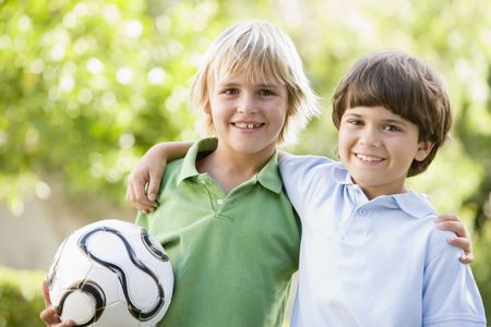 Two young boys outdoors with soccer ball smiling Stock Photo - 3487153