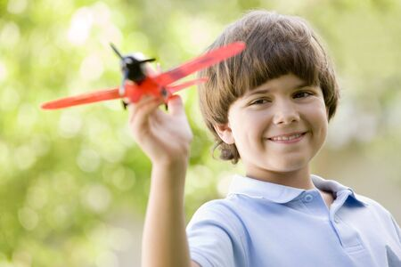 toy plane: Young boy with toy airplane outdoors smiling