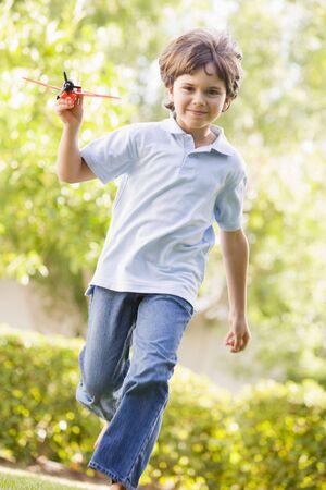 ni�os jugando en el parque: Chico joven con avi�n de juguete al aire libre, corriendo sonriente