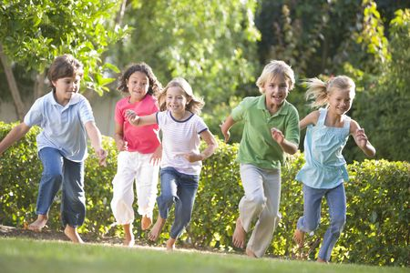 Five young friends running outdoors smiling photo