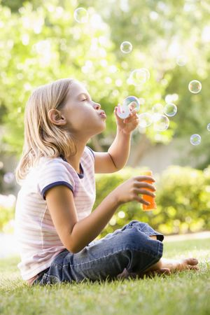 girl blowing: Young girl blowing bubbles outdoors