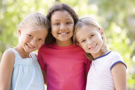 best friends girls: Three young girl friends standing outdoors smiling
