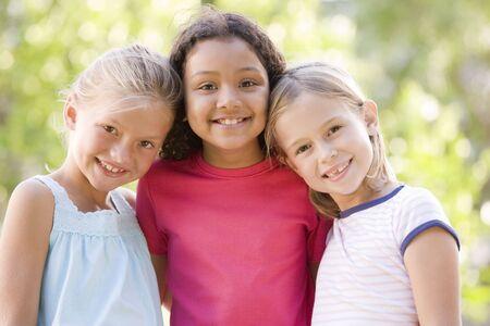 mejores amigas: Tres j�venes amigos de pie muchacha sonriente al aire libre  Foto de archivo