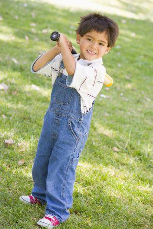 Young boy holding baseball bat outdoors smiling photo