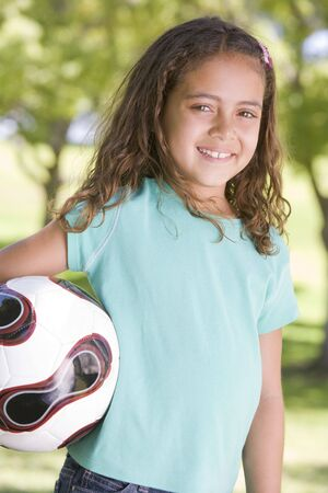 Young girl holding soccer ball outdoors smiling photo