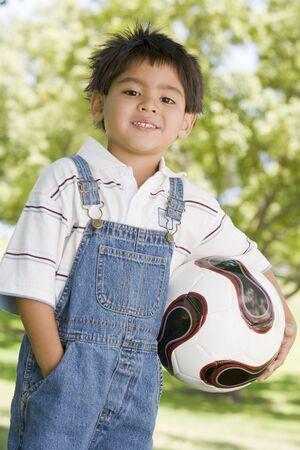 ni�os jugando en el parque: Chico joven la celebraci�n de bal�n de f�tbol al aire libre sonriente