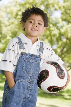 Young boy holding soccer ball outdoors smiling photo