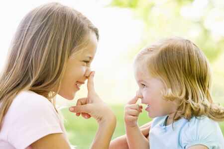 countryside loving: Two sisters playing outdoors and smiling Stock Photo