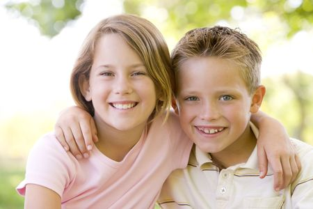 countryside loving: Brother and sister sitting outdoors smiling Stock Photo