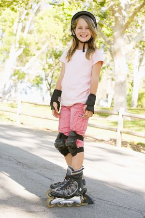 skate park: Young girl outdoors on inline skates smiling