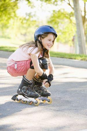 schaatsen: Jong meisje buiten op inline skates glimlachende