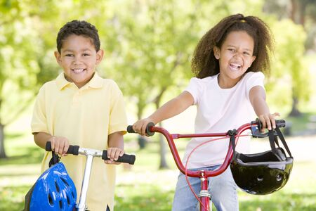 Brother and sister outdoors with scooter and bicycle smiling photo
