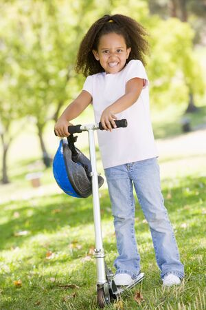 Young girl outdoors on scooter smiling Stock Photo - 3488002