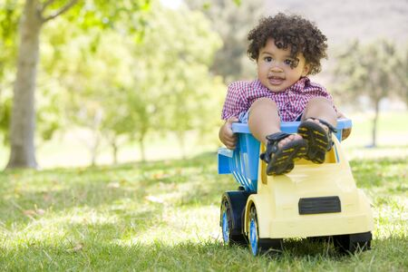 Young boy outdoors playing on toy dump truck smiling photo