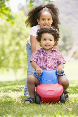 Sister pushing brother on toy with wheels smiling photo