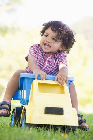 toy truck: Young boy playing on toy dump truck outdoors