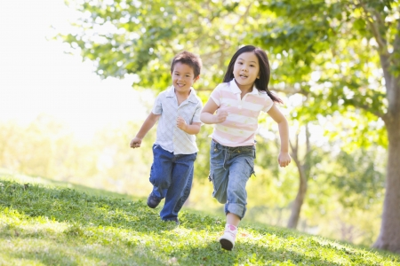 sibling: Brother and sister running outdoors smiling Stock Photo