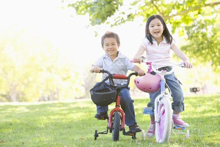 Brother and sister outdoors on bicycles smiling photo