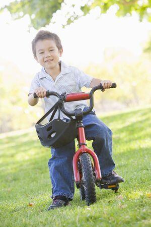 stabilizers: Chico joven en bicicleta al aire libre sonriente  Foto de archivo