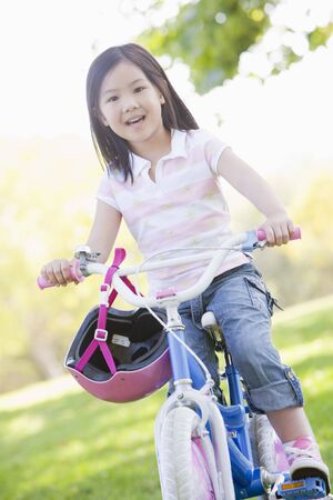 Young girl on bicycle outdoors smiling photo